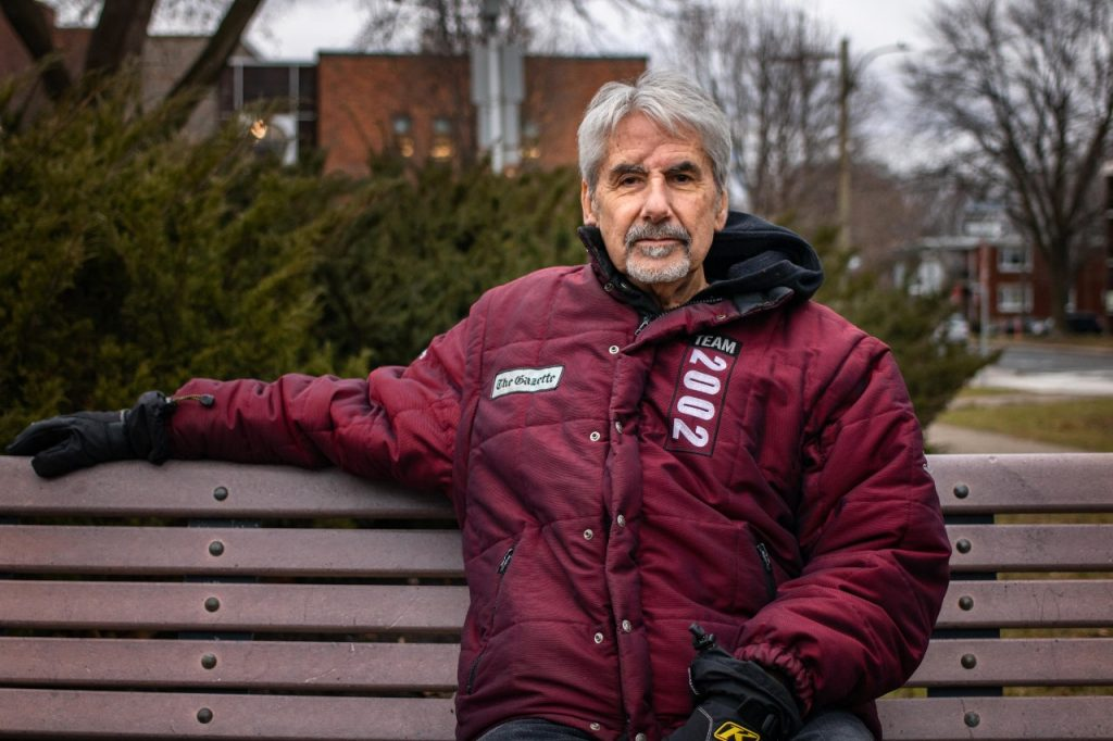 A man sits on a bench and looks at the camera