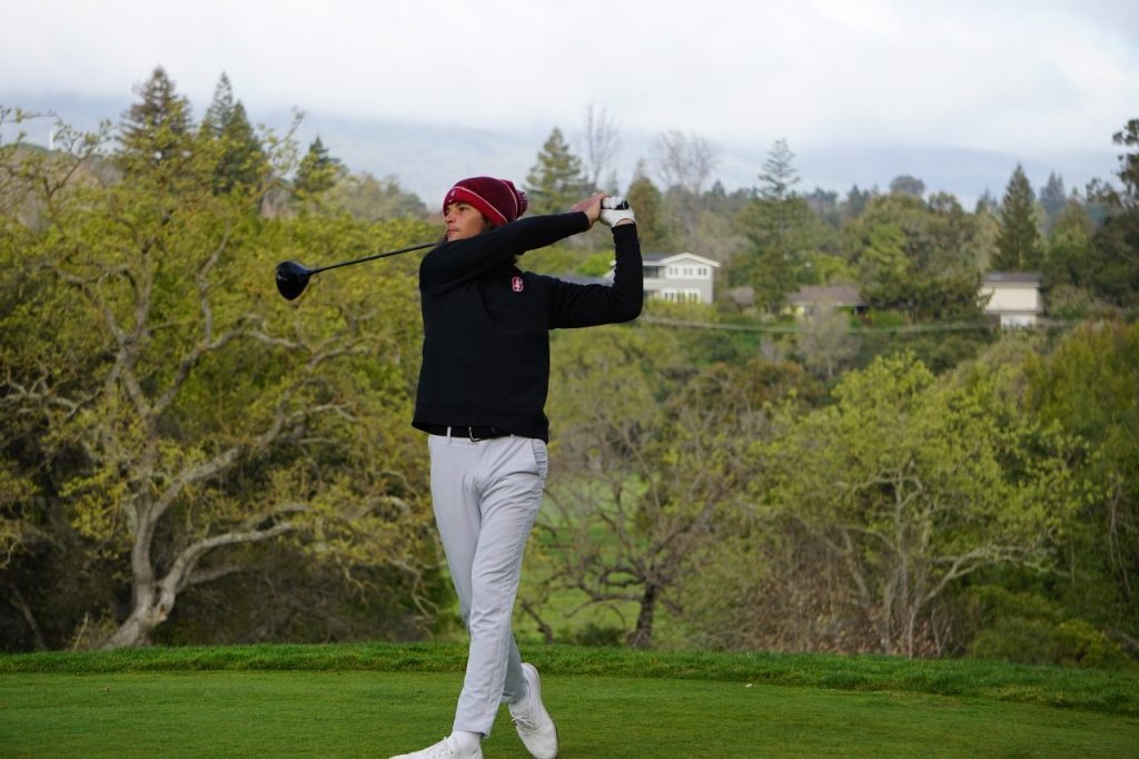 A golfer in black long sleeve top and khaki pants takes a swing.