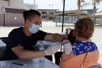 A woman receives a vaccine shot.
