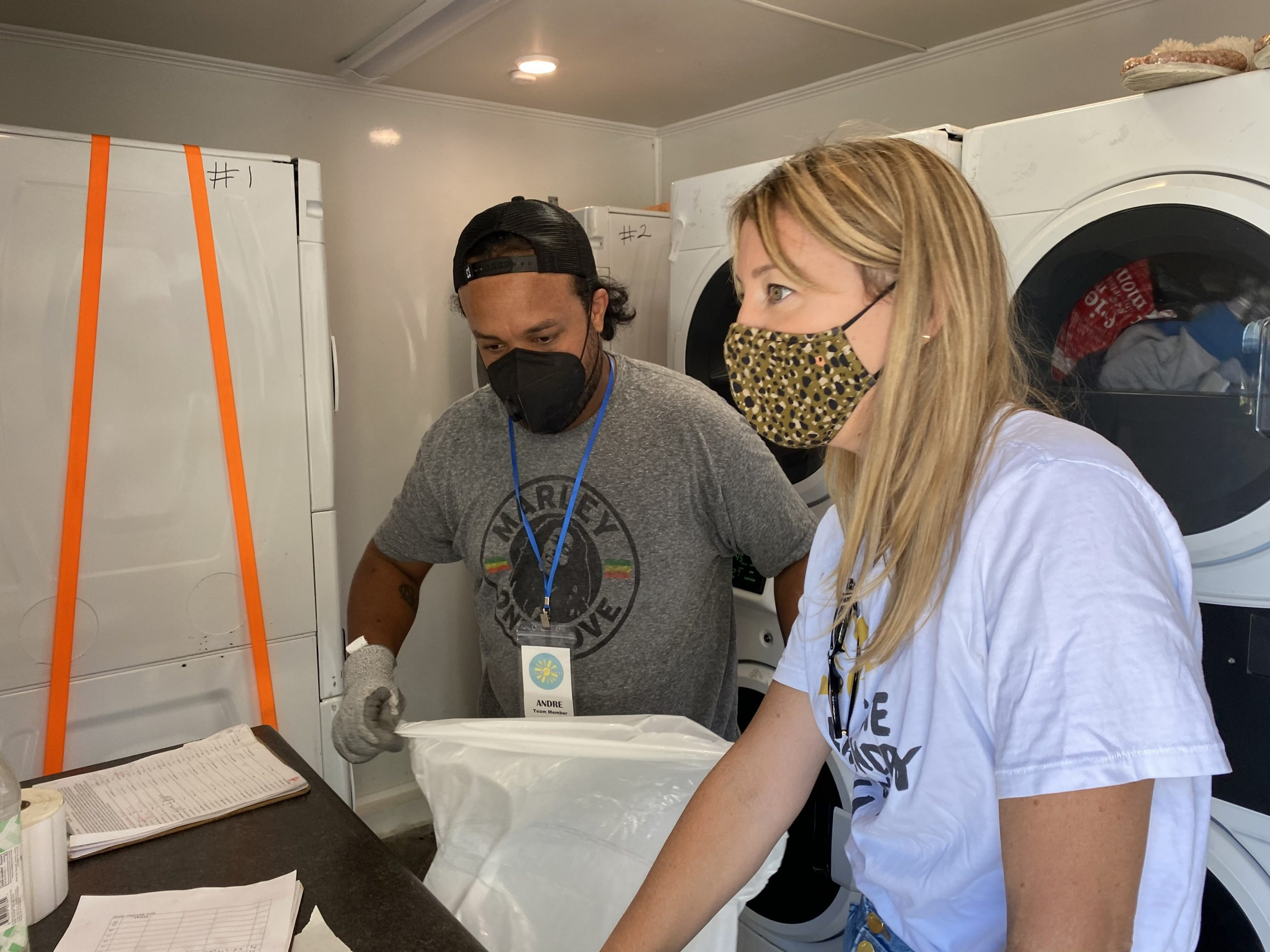 Jodie Dolan (right), the founder of The Laundry Truck LA, sorts clothes at a vaccination site at MacArthur Park. (Photo courtesy of The Laundry Truck LA.)