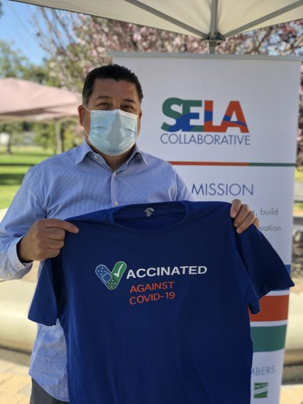 A man holds up a celebratory t-shirt after receiving his COVID-19 vaccine at a mobile clinic run by the SELA Collaborative in South Gate, Calif. (Photo courtesy of the SELA Collaborative.)
