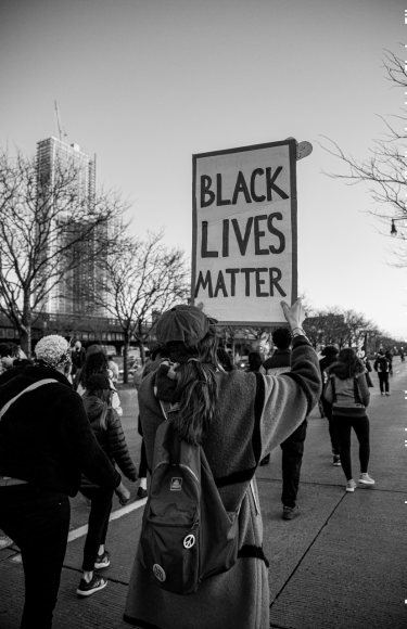 A protester marches down the Westside Highway with a 'Black Lives Matter' sign. (Iman Floyd-Carroll/Peninsula Press)