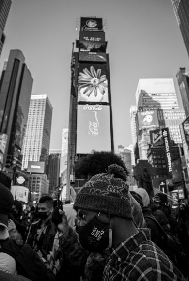 """A male protester with a face mask emblazoned with the words """"Black Lives Matter"""" stands against the backdrop of Times Square during opening remarks at the Justice for Breonna Taylor protest on March 13, 2021. (Iman Floyd-Carroll/Peninsula Press)"""