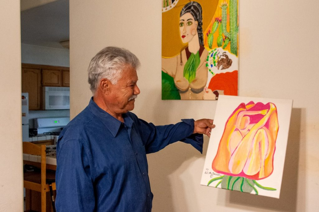 A man with gray hair hold sup a painting of a flower. In the background is another painting of a woman with the Mexican flag and cacti.