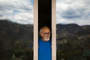 A man looks out from sliding doors.