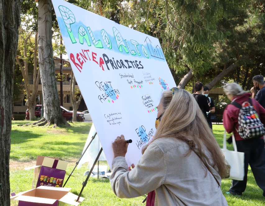 A woman is squatting down and writing on a poster board