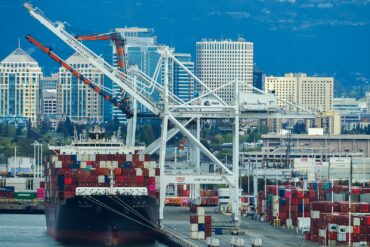 A container ship and cranes, with downtown Oakland and the Oakland Hills in the background.