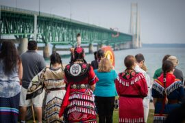 Indigenous ceremony being performed at the Straits of Mackinac. Photo of people's back in the foreground with the Mackinac Bridge in the background.